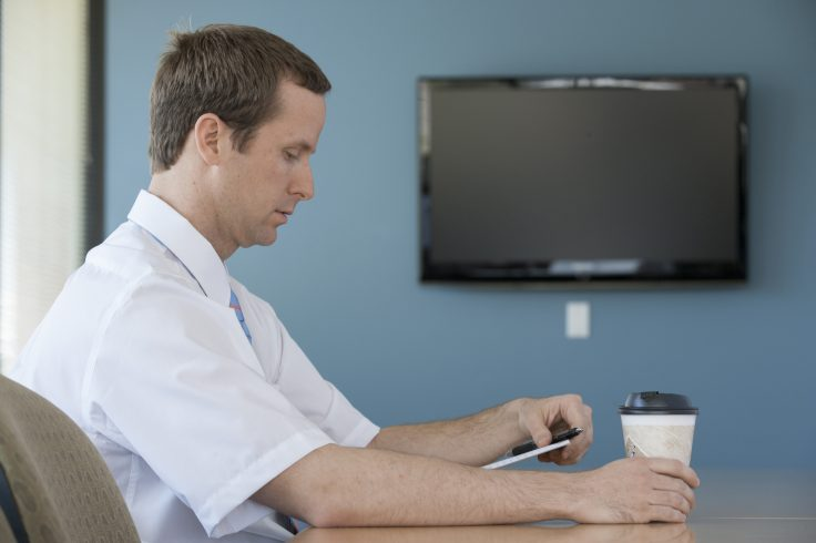 man-checking-notes-in-office_BYicblCHi-736x490